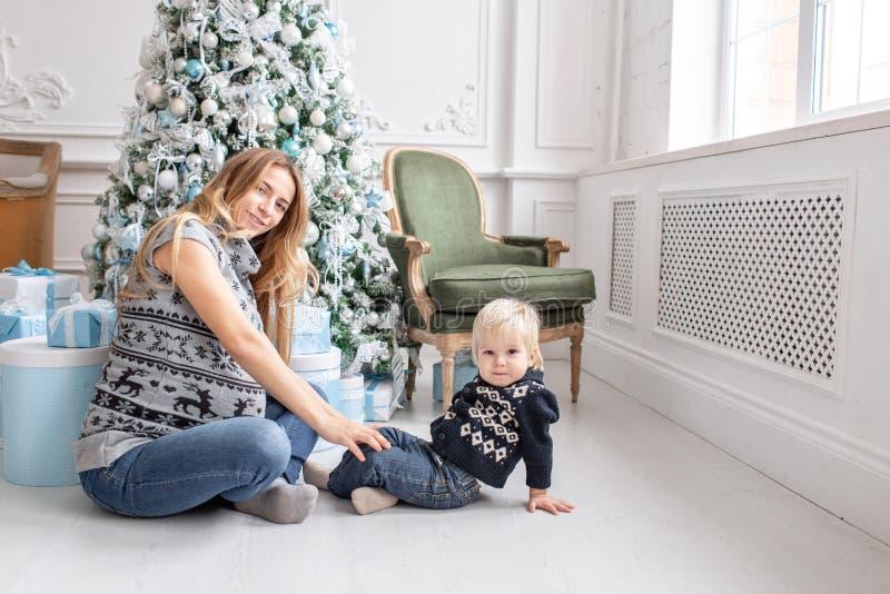 Jogos da mamã com criança Assento no assoalho Retrato feliz da família na casa - a mãe grávida nova abraça seu pequeno imagens de stock royalty free