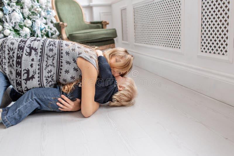Jogos da mamã com criança Encontro no retrato feliz da família do assoalho na casa - a mãe grávida nova abraça seu filho pequeno imagens de stock royalty free