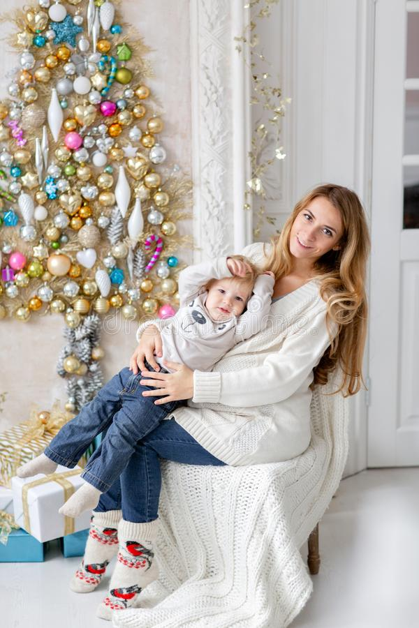 Jogos da mamã com criança Retrato feliz da família na casa - a mãe grávida dos jovens abraça seu filho pequeno Ano novo feliz imagem de stock