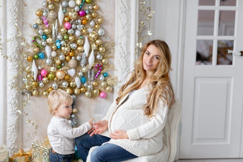 Jogos da mamã com criança Retrato feliz da família na casa - a mãe grávida dos jovens abraça seu filho pequeno Ano novo feliz imagem de stock royalty free