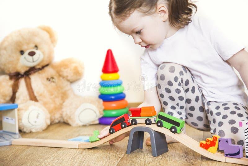 Jogos da menina com brinquedos, a estrada de ferro de madeira e o trem fotografia de stock