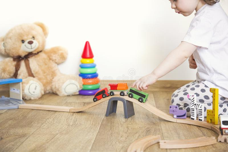 Jogos da menina com brinquedos, a estrada de ferro de madeira e o trem imagens de stock