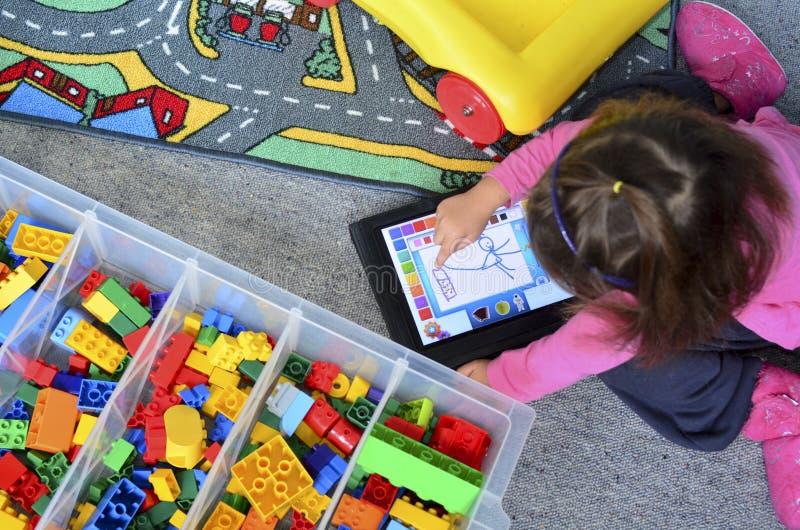 Jogos da menina com iPad imagem de stock