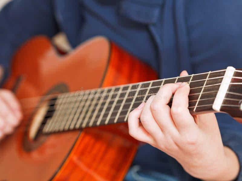 Jogos da mulher na guitarra acústica clássica imagens de stock
