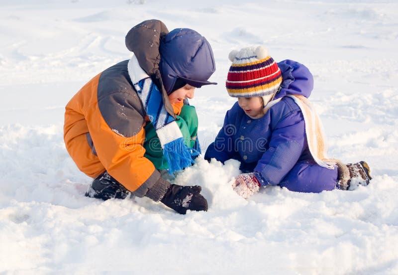 Jogos de crianças à neve fotografia de stock royalty free
