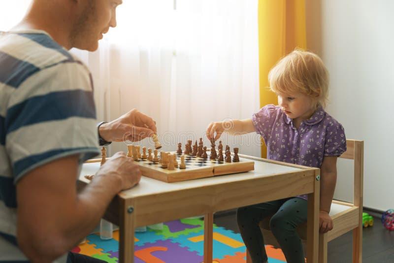 Jogos do cérebro - o pai ensina para jogar a xadrez para sua criança foto de stock