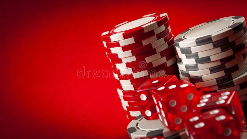Jogos do casino e conceito de jogo com as microplaquetas de pôquer empilhadas e os dados vermelhos usados no jogo dos excrementos imagem de stock