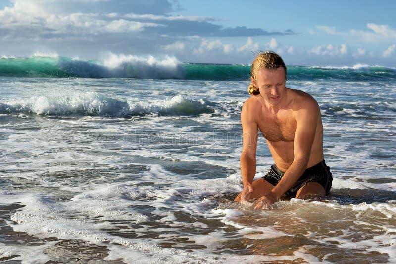 Jogos do homem novo na água de mar imagens de stock royalty free