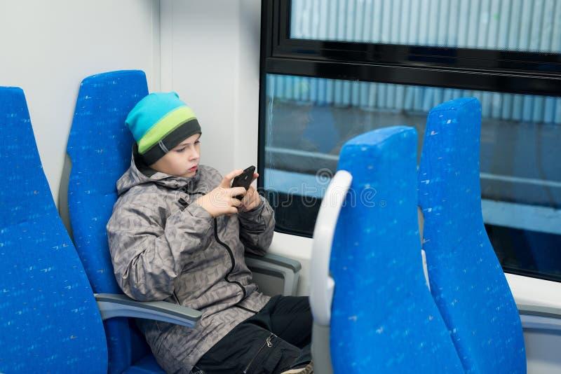 jogos do menino no smartphone no trem imagens de stock royalty free