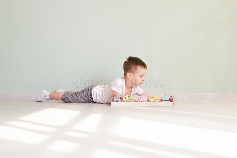 Jogos do rapaz pequeno com carro do brinquedo em casa imagem de stock
