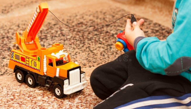 Jogos do rapaz pequeno com carro do brinquedo fotografia de stock royalty free