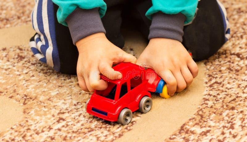 Jogos do rapaz pequeno com carro do brinquedo foto de stock
