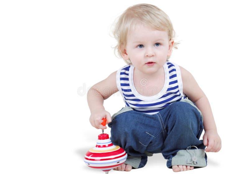 Jogos do rapaz pequeno com pegtop imagens de stock royalty free