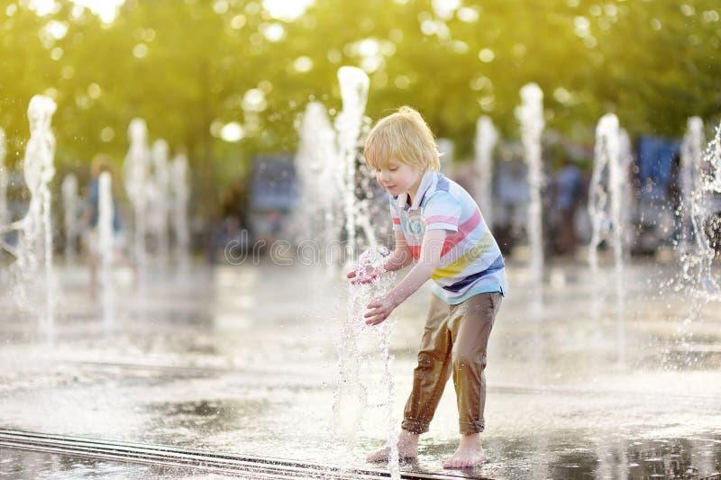 Jogos do rapaz pequeno no quadrado entre os jatos de água na fonte no dia de verão ensolarado fotografia de stock royalty free