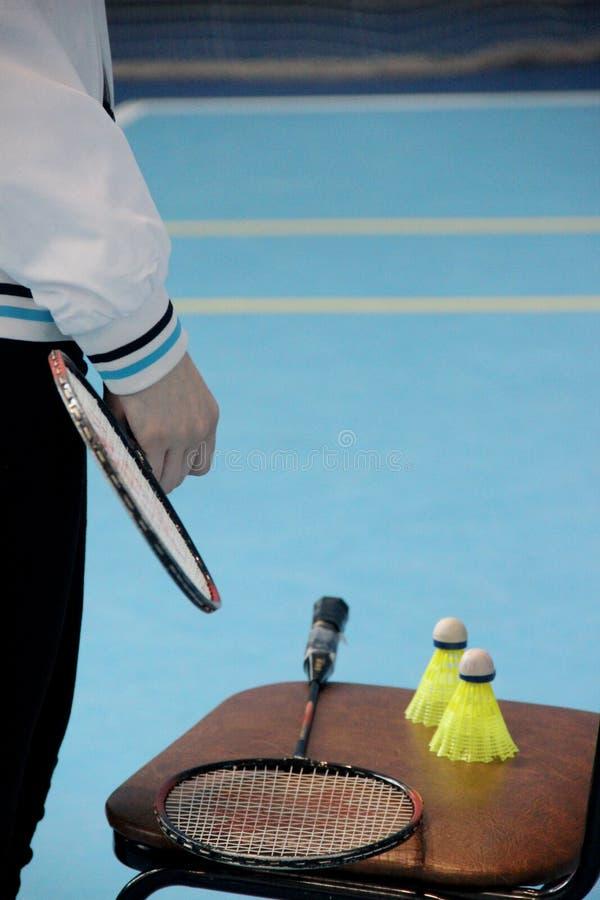Jogos e competições dos esportes O adolescente guarda uma raquete de badminton com seus dedos, duas petecas, raquete na imagens de stock