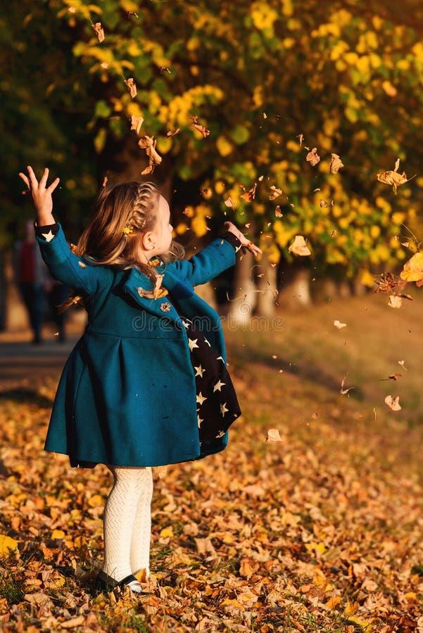 Jogos elegantes da menina com folhas de outono Criança feliz ao ar livre O outono caçoa a forma Feriados do outono Copie o espaço foto de stock
