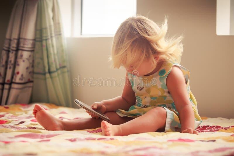 jogos louros da menina com smartphone imagem de stock royalty free