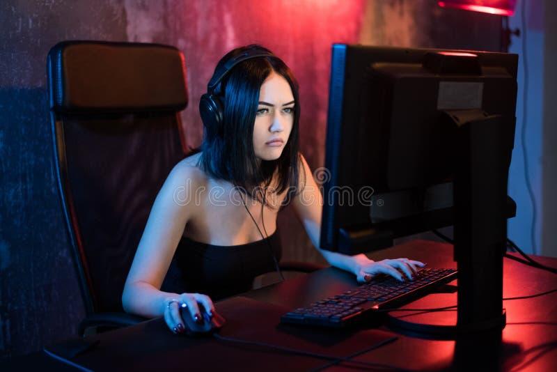 Jogos profissionais do Gamer da menina em MMORPG ou jogo de vídeo da estratégia em seu computador Ela ` s que participa no Cyber  foto de stock