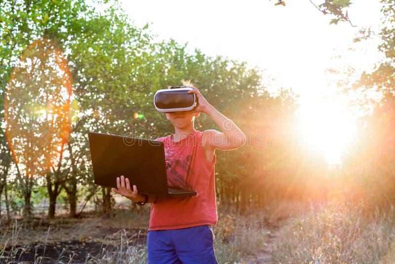 Jogos virtuais baseados na realidade Um menino na natureza no espa?o virtual, vidros de VR, uma floresta, um port?til fotografia de stock