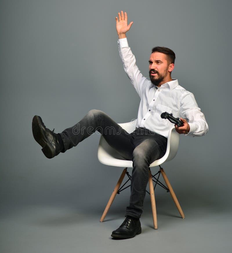 Jogue o console do jogo emocionalmente Homem segurando um joystick e gesticulando com pernas e braços Perder um jogo de computado foto de stock royalty free
