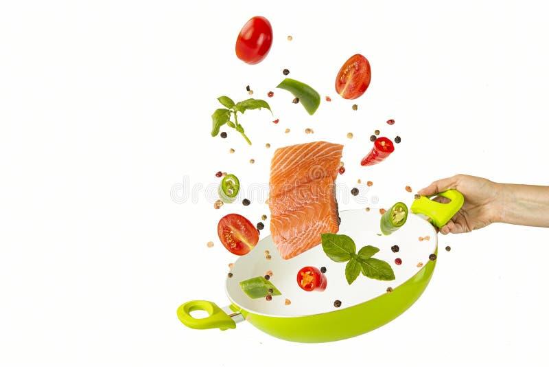 Jogue os peixes e os vegetais com as especiarias na frigideira verde objetos no fundo branco Alimento do voo fotos de stock royalty free