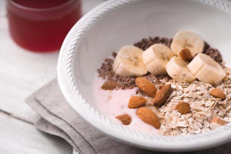 Jogurt alla frutta con differenti guarnizioni sull'orizzontale di legno bianco della tavola fotografia stock