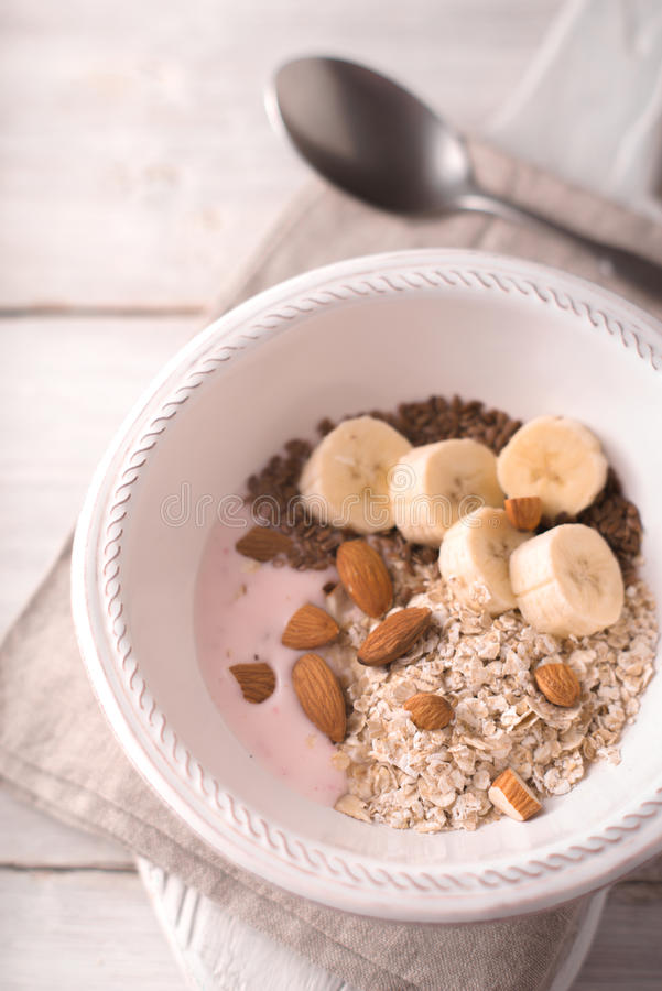 Jogurt alla frutta con differenti guarnizioni sulla vista di legno bianca del piano d'appoggio immagine stock