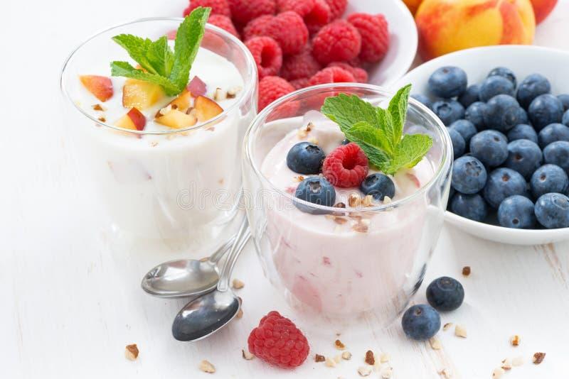 Jogurt alla frutta e della bacca ed ingredienti freschi sulla tavola bianca fotografia stock