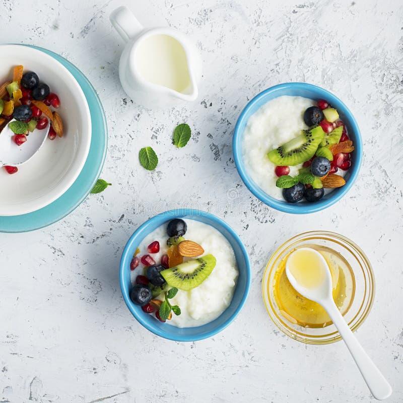 Jogurt, dojna owsianka, granola dla śniadania z różnymi jagodami, dokrętki i owoc: kiwi, granatowiec, wysuszone morele obrazy royalty free
