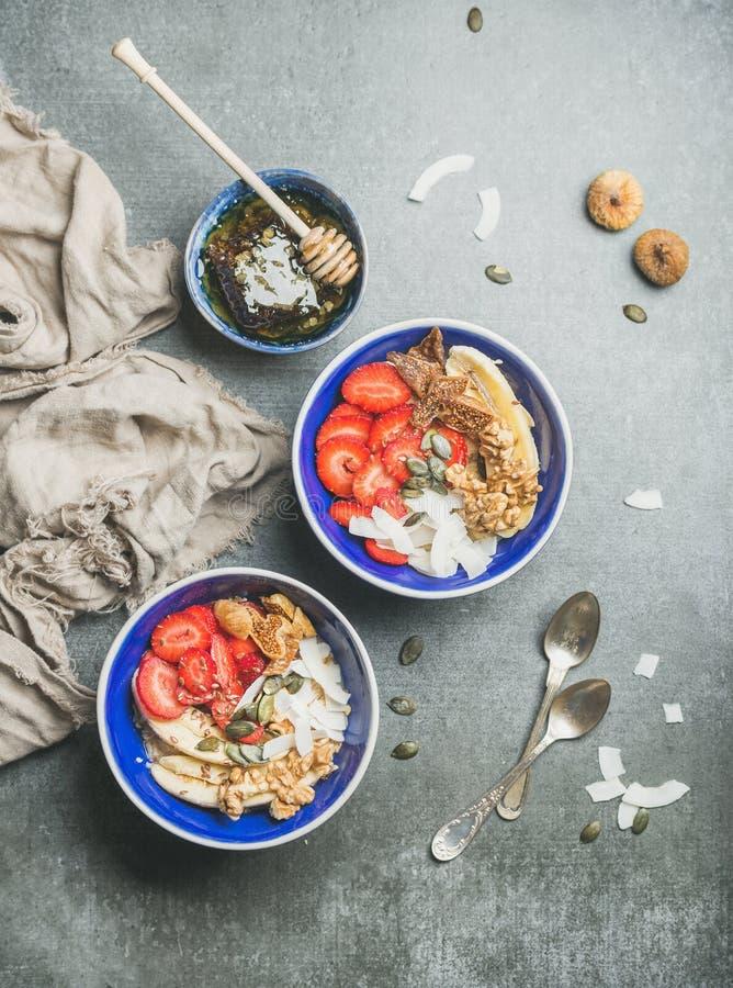 Jogurt, granola, ziarna, owoc i miód w błękitnych ceramicznych pucharach, zdjęcie royalty free