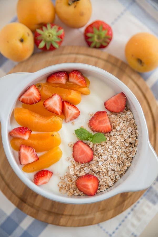 Jogurt mit Granola, Erdbeeren und Aprikosen lizenzfreies stockbild