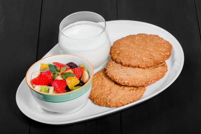 Jogurt mit Obstsalat- und Haferplätzchen auf Platte auf dunklem hölzernem Hintergrund Frisches gesundes Frühstück lizenzfreie stockfotos