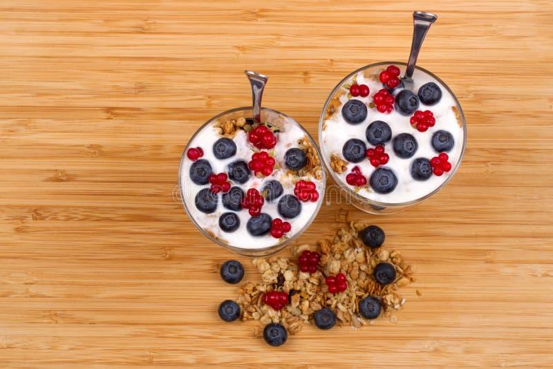 Jogurt, muesli und Beeren der Blaubeere, Sumpfheidelbeere und Stein stockfoto