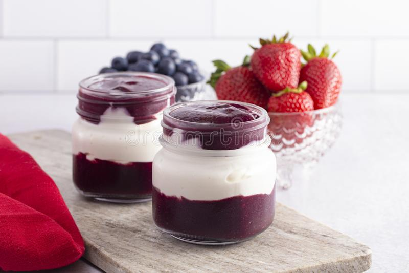 Jogurt und Berry Puree in einem Glasgefäß zum Frühstück stockfoto