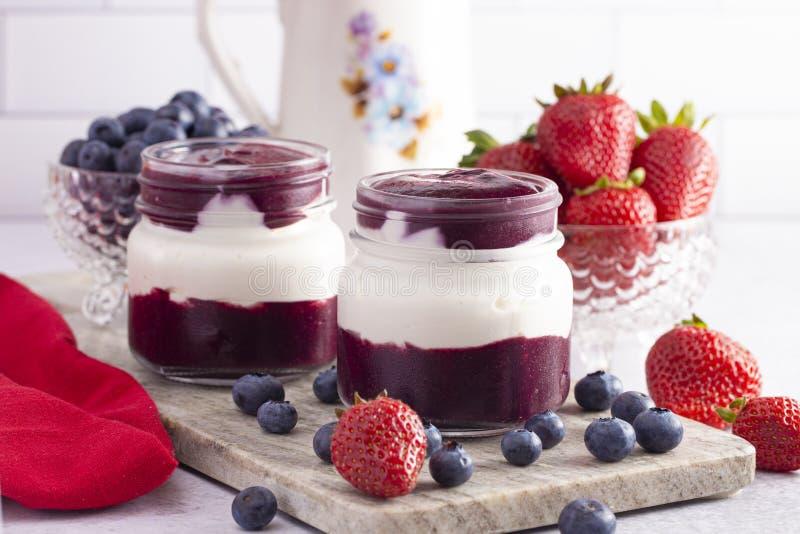 Jogurt und Berry Puree in einem Glasgefäß zum Frühstück lizenzfreies stockfoto