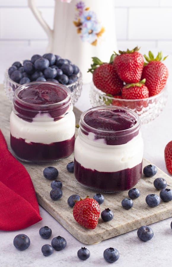 Jogurt und Berry Puree in einem Glasgefäß zum Frühstück stockfotos