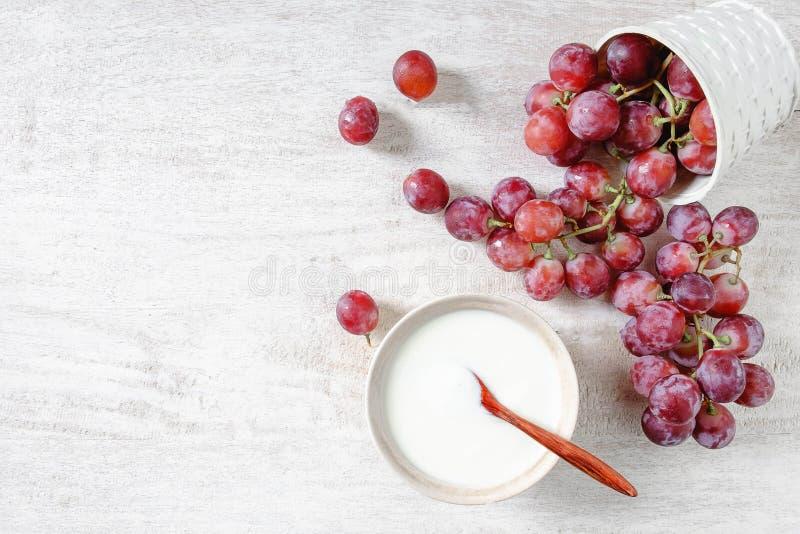 Jogurt und gesundes Frühstück der roten Trauben stockbild