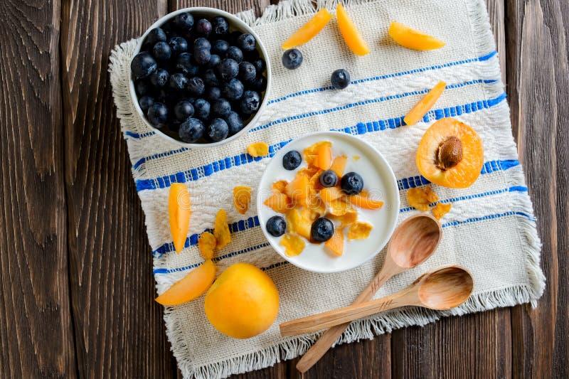 Jogurt z świeżymi czarnymi jagodami, kukurydzanymi płatkami i morelami, odgórny widok obraz royalty free