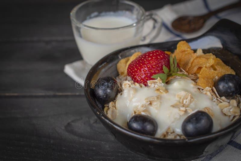 Jogurtmischungshafermehl, Erdbeere und Traubenbelag in der schwarzen Schüssel auf blauem und weißem gestreiftem Gewebe und hölzer lizenzfreies stockbild
