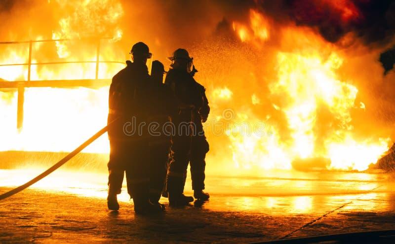 JOHANNESBURG, AFRIQUE DU SUD - mai 2018 sapeurs-pompiers se tenant devant le feu avec le tuyau pendant un exercice d'entraînement photographie stock