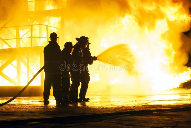 JOHANNESBURG, SÜDAFRIKA - Mai 2018 Feuerwehrmänner, die Wasser am Feuer während einer feuerbekämpfenden Schulungsübung sprühen stockfoto