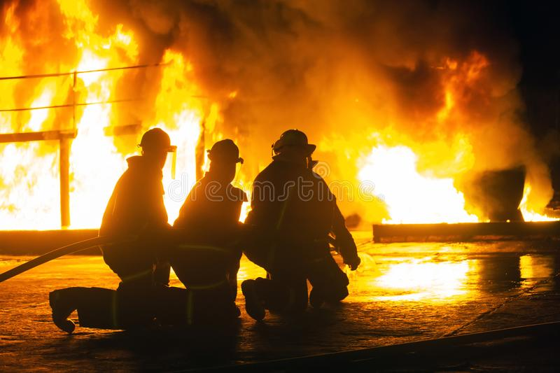 JOHANNESBURG, SOUTH AFRICA - MAY, 2018 Firefighters kneeling in front of burning structure during a fighting training exercise stock photo