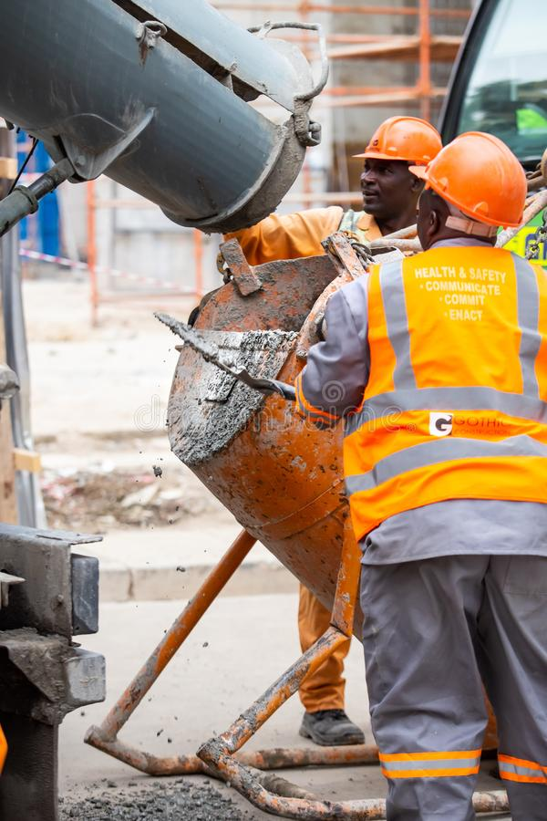 Cement filling on construction site. Johannesburg, South Africa, 22nd March- 2019: Construction workers filling up cement mixer on construction site royalty free stock images