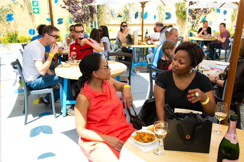 African Female Friends eating, drinking and generally enjoying a day out at a Food and Wine Fair. Johannesburg, South Africa - November 9 2013: African Female royalty free stock photography