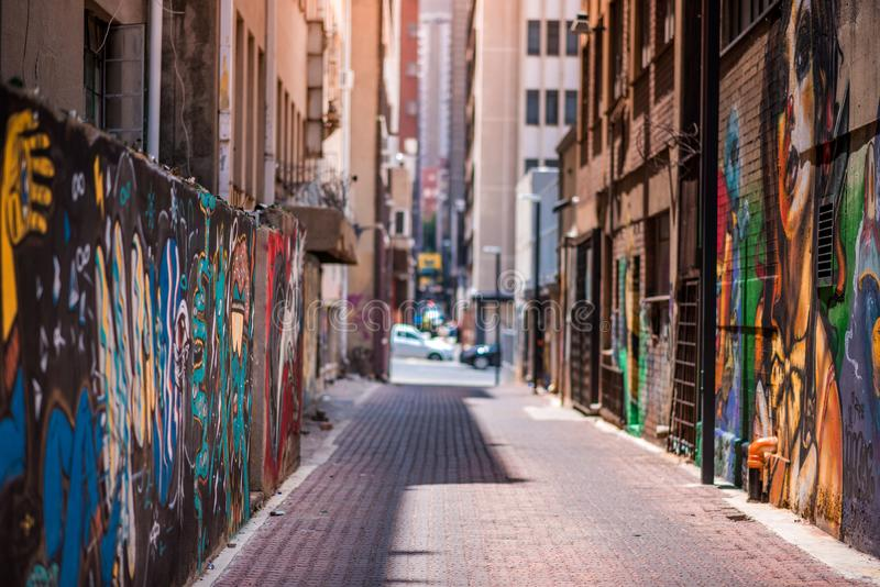 An alleyway in Johannesburg inner city with graffiti on the walls. Johannesburg / South Africa - November 19 2016: An alleyway in Johannesburg inner city with stock photo