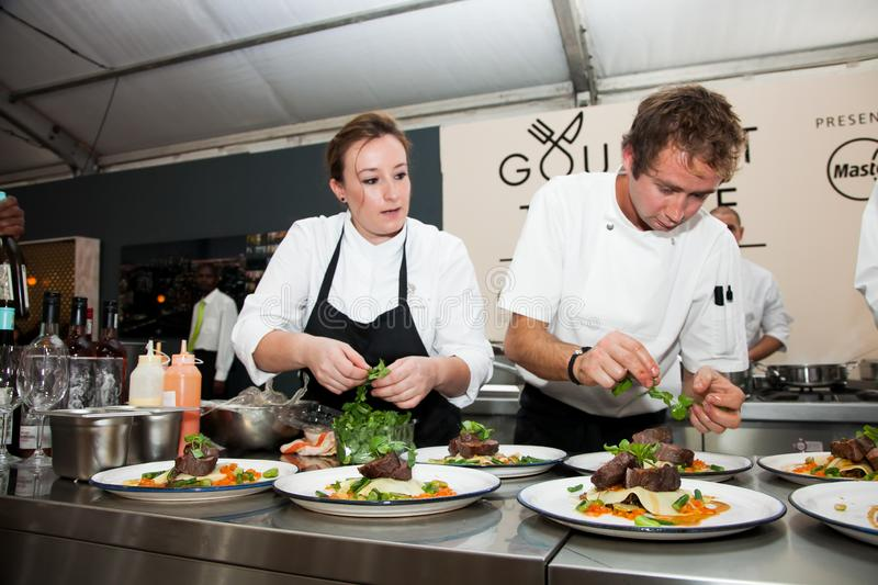 Chefs making and serving gourmet meals at food festival vendor stall royalty free stock images