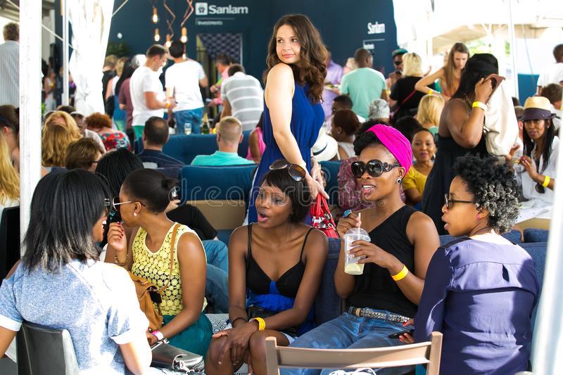 Diverse Friends eating, drinking and generally enjoying a day out at a Food and Wine Fair. Johannesburg, South Africa - November 9 2013: Diverse Friends eating stock photos