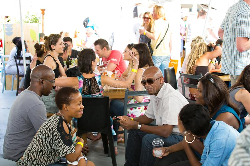 Diverse Friends eating, drinking and generally enjoying a day out at a Food and Wine Fair. Johannesburg, South Africa - November 9 2013: Diverse Friends eating royalty free stock image