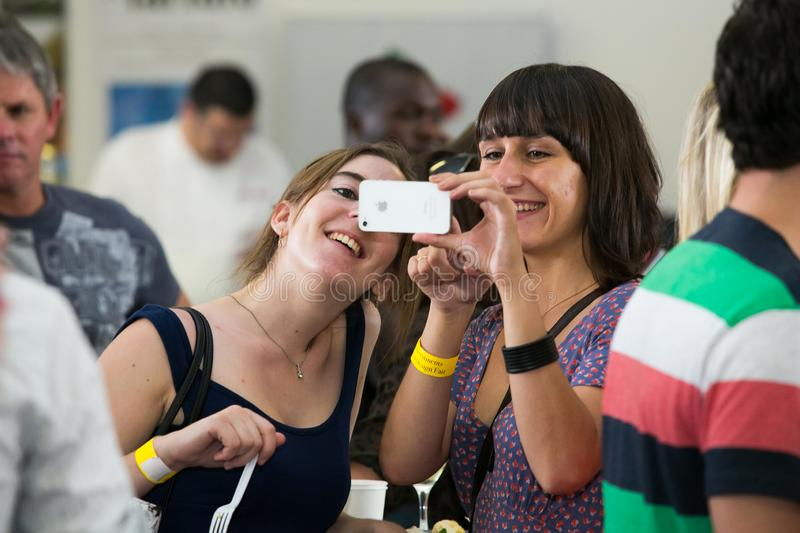 Friends taking a selfie on their phone and generally enjoying a day out at a Food and Wine Fair. Johannesburg, South Africa - November 9 2013: Friends taking a stock image