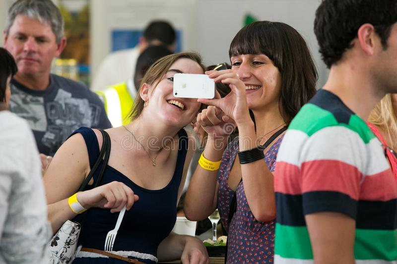 Friends taking a selfie on their phone and generally enjoying a day out at a Food and Wine Fair. Johannesburg, South Africa - November 9 2013: Friends taking a royalty free stock photos